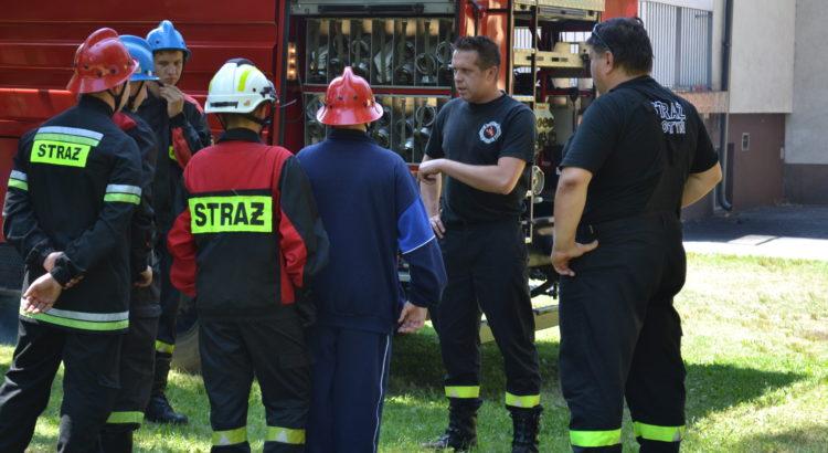 Dwóch strażaków z OSP Gostyń prowadzi szkolenie, wokół nich stoi młodzież, a za nimi widać samochód pożarniczy.