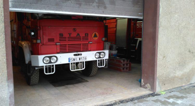Wóz gaśniczy GBA 2,5/16 marki Star stoi w garażu, którego brama się otwiera.